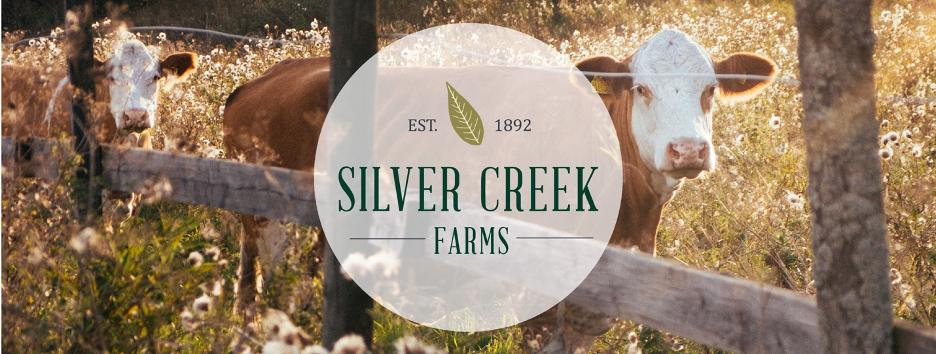 Silver Creek Farms logo over a farm field with two cows